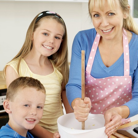 Woman using wooden ladle, boy and girl smiling at the camera photo