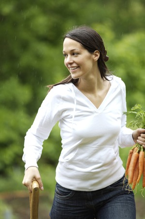 Woman holding carrots and spading fork