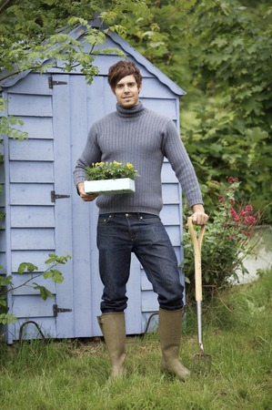 spading fork: Man with potted flower and spading fork