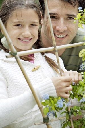 Girl and man looking through wooden post with flowers photo