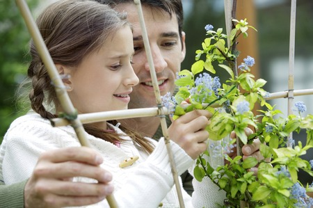 Girl and man looking at flowers twirled around wooden post photo