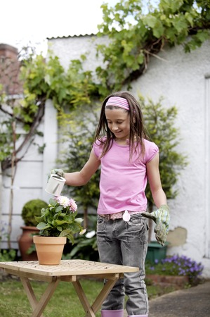 gardening gloves: Girl with gardening gloves watering a pot of flowers