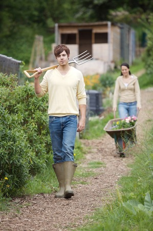 Man holding spading fork, woman pushing wheelbarrow with potted flowers in the background Stock Photo