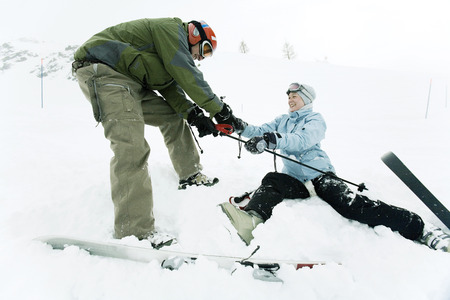 Male skier helping female skier Stock Photo