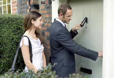 Businessman knocking on the door while businesswoman waits by the side photo