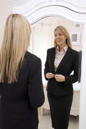 blazer: Woman buttoning her blazer while looking at the mirror