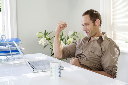 jubilating: Man working in a home office