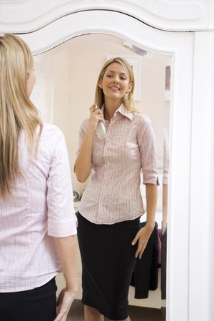 Woman spraying perfume on her neck while looking at the mirror photo