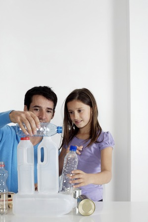 stacking: Girl and man stacking empty bottles