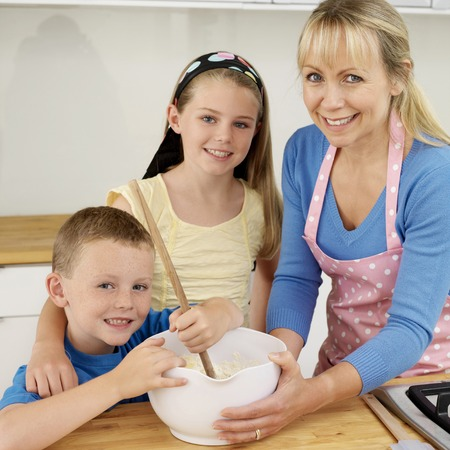 Boy using wooden ladle, woman and girl smiling at camera photo