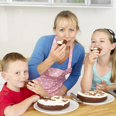 Woman with boy and girl enjoying cakes in the kitchen photo