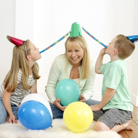 Boy and girl blowing party horn blowers, woman holding balloon photo