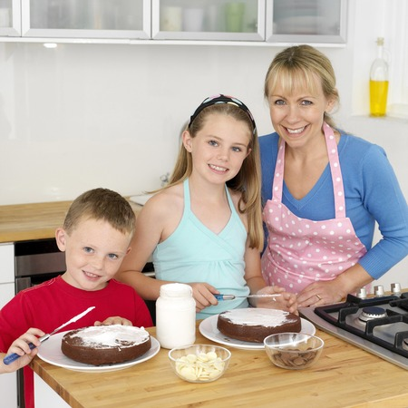 Boy and girl spreading cream on cake, woman smiling at the camera photo