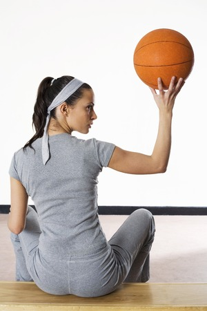 Woman sitting on bench holding up basketball photo