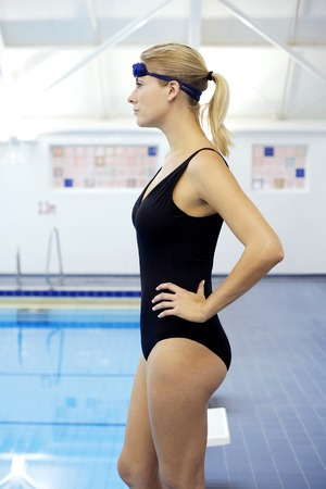 arms akimbo: Woman in swimsuit standing with her arms akimbo