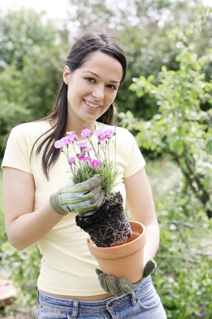 gardening gloves: Woman with gardening gloves holding a pot flower Stock Photo