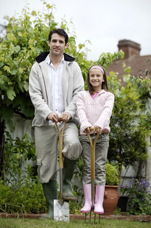 Man and girl stepping on gardening tools