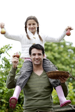 Girl sitting on man's shoulders holding up pears photo