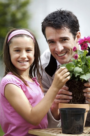 Man and girl planting flower into flower pot photo