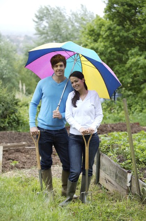 spading fork: Man with long-handled spade and woman with spading fork sharing an umbrella