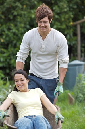 Man pushing wheelbarrow with woman in it photo