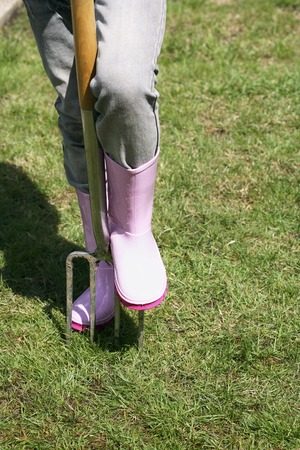 spading fork: Unrecognizable person with gardening boots and spading fork