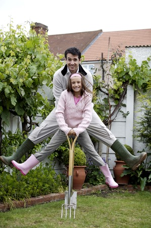Man and girl jumping up while holding onto gardening tools