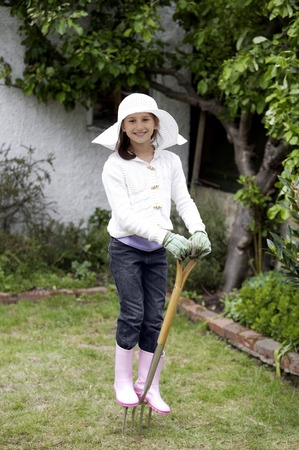 Girl with straw hat, gardening gloves and boots standing on a pitchfork Stock Photo
