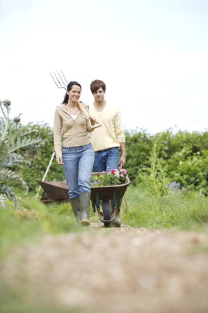 Man pushing wheelbarrow with potted flowers, woman holding spading fork