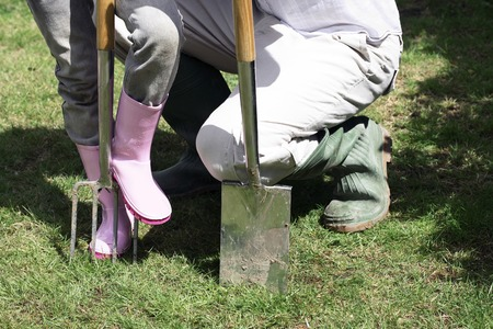 Unrecognizable people with gardening boots and tools