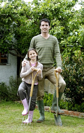 spading fork: Man and girl stepping on gardening tools