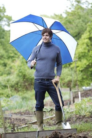 long handled: Man with umbrella holding long-handled spade
