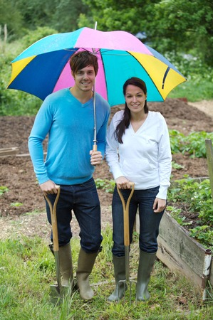 Man with long-handled spade and woman with spading fork sharing an umbrella