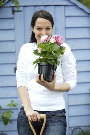 spading fork: Woman with spading fork and potted flower Stock Photo