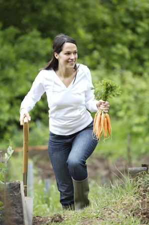 spading fork: Woman holding carrots and spading fork