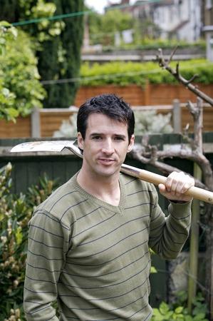 long handled: Man holding a long-handled spade on his shoulder
