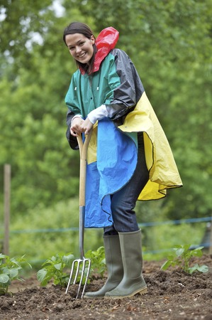 spading fork: Woman in raincoat smiling at the camera while using spading fork Stock Photo