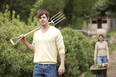 spading fork: Man holding spading fork, woman pushing wheelbarrow with potted flowers in the background Stock Photo