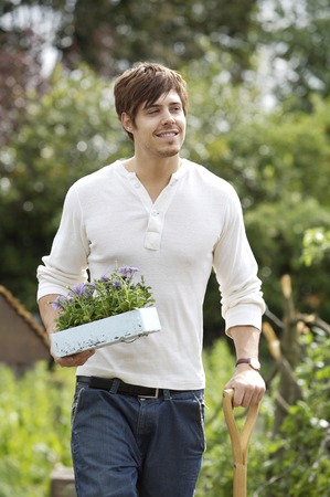 spading fork: Man holding potted plant and spading fork