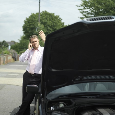inconvenience: Businessman talking on the phone beside a broken down car
