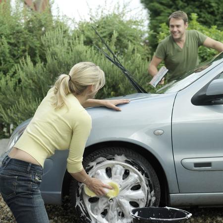 Woman washing car wheel, man washing windshield with squeegee photo