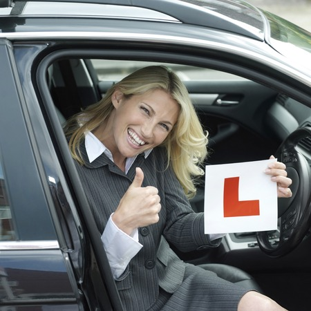 l plate: Businesswoman showing thumbs up while holding L plate Stock Photo