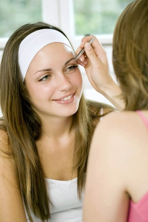 self conceit: Girl helping another girl tweezing her eyebrows Stock Photo