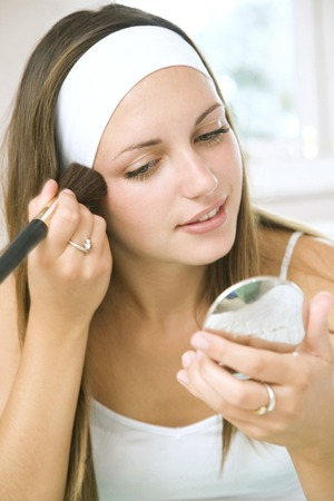 self conceit: Girl applying blusher while looking at compact mirror