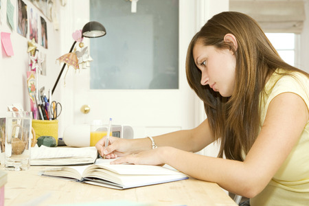 assignment: Girl doing assignment in her room Stock Photo