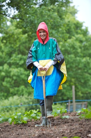 spading fork: Woman in raincoat holding a spading fork Stock Photo