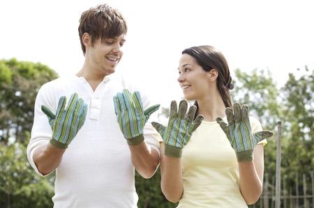 Hombre y una mujer mirando su sucio guantes de jardinería