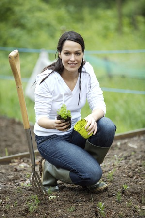 spading fork: Woman with potted plant and spading fork