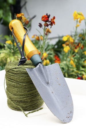 Hand trowel resting on a roll of twine photo