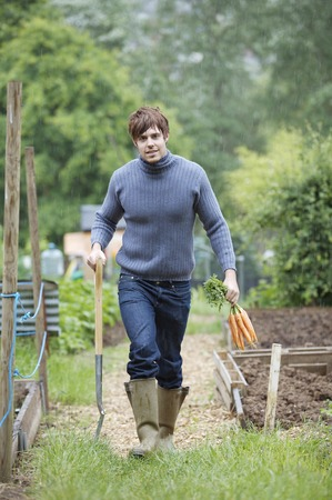 Man with spading fork and carrots walking in the garden